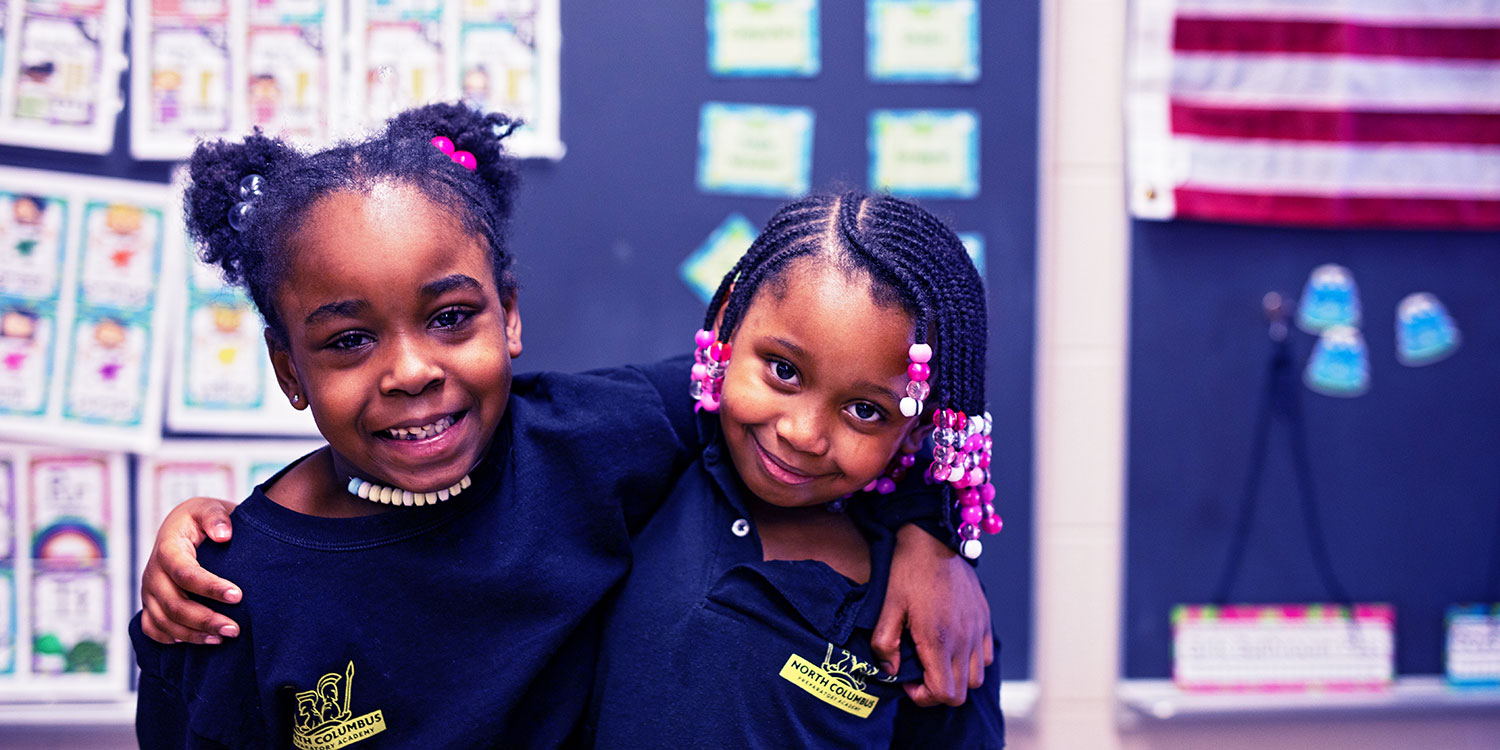 Smiling students with arms around each other.