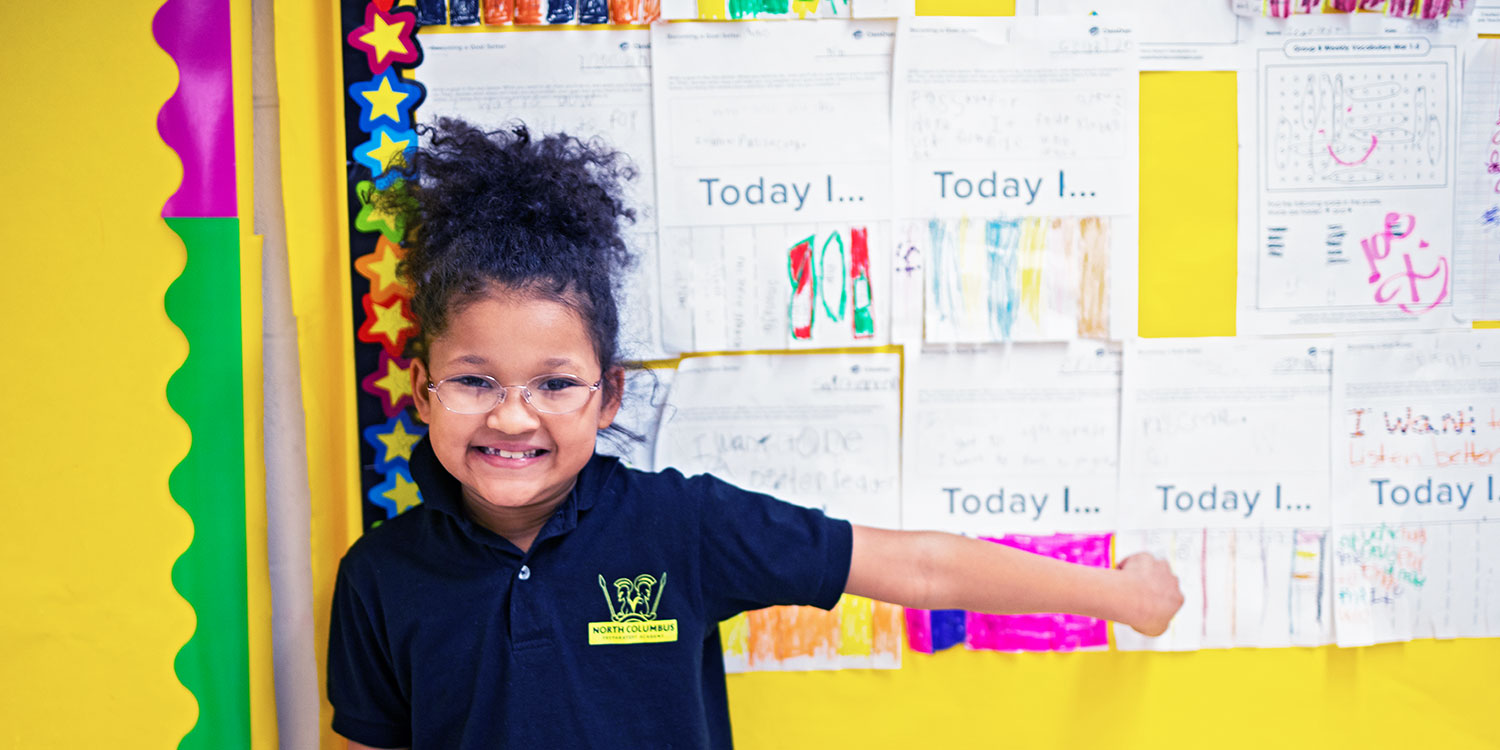Elementary student smiling and pointing to work on a bulletin board.