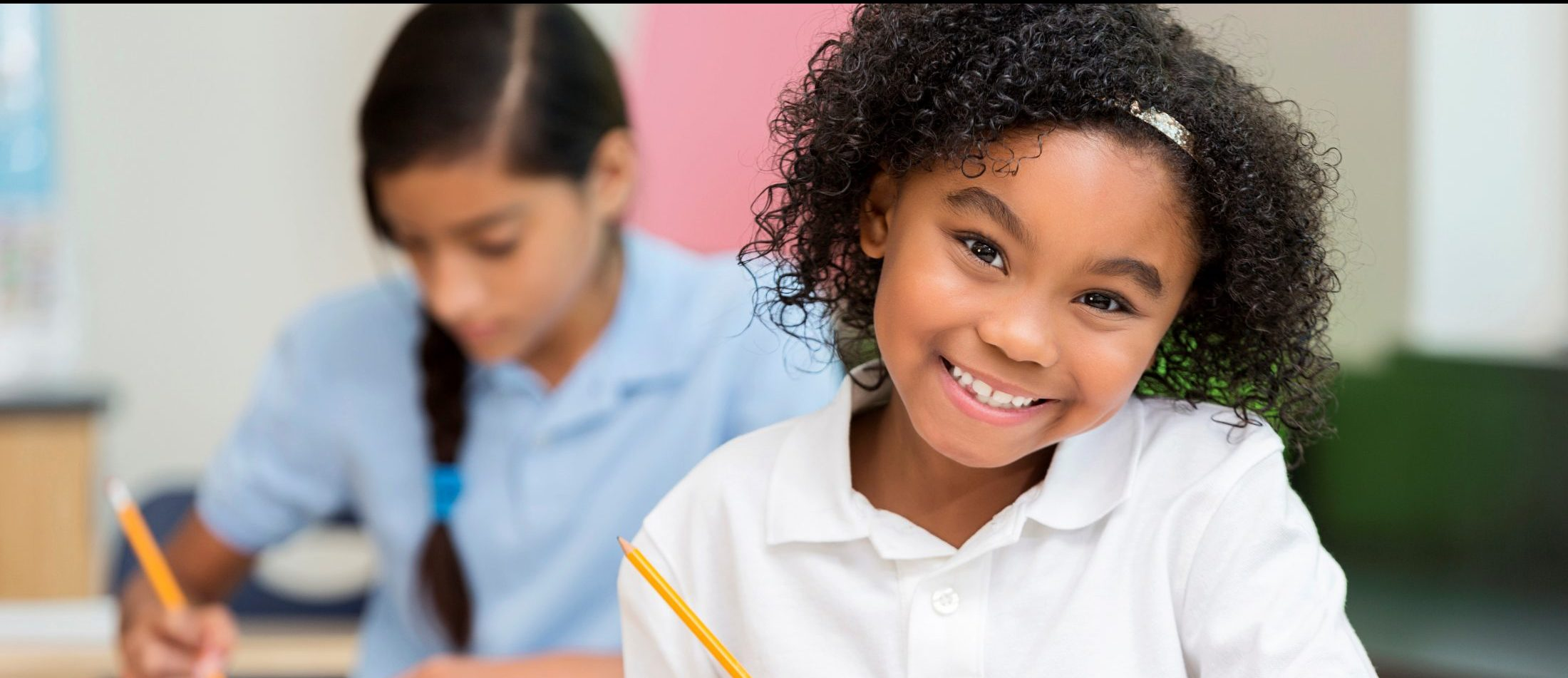 Elementary student smiling at desk.