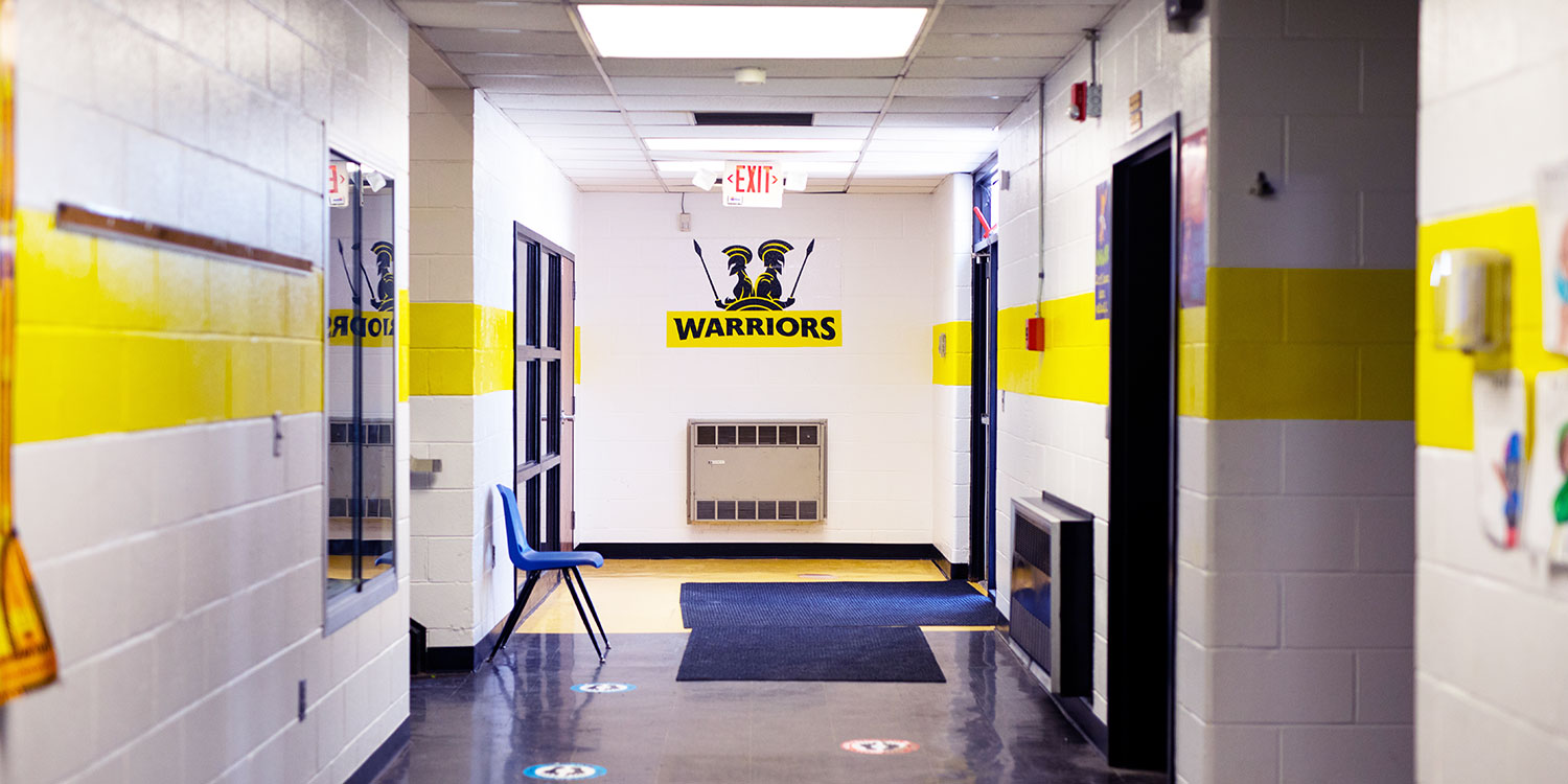 Hallway with NCPA Warriors logo painted on wall.