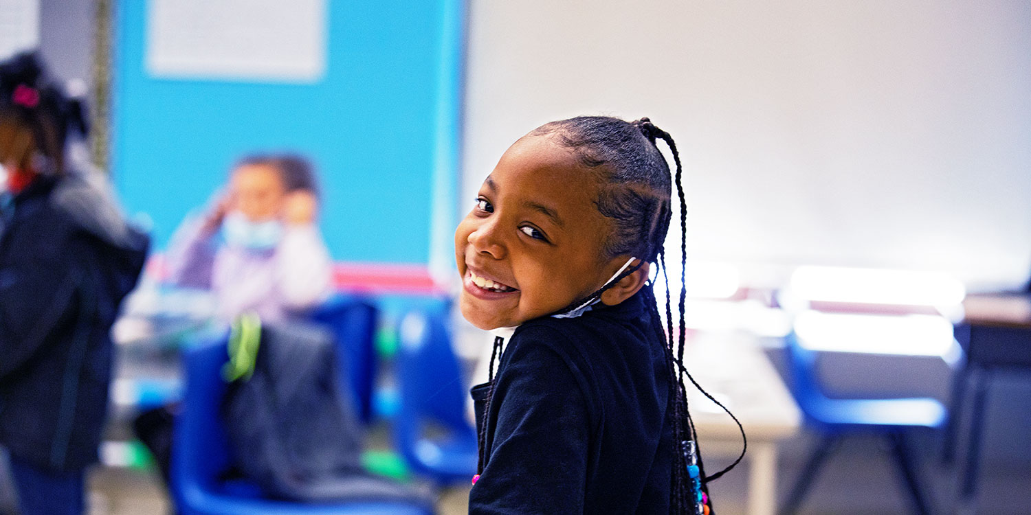 Elementary student smiling in classroom.