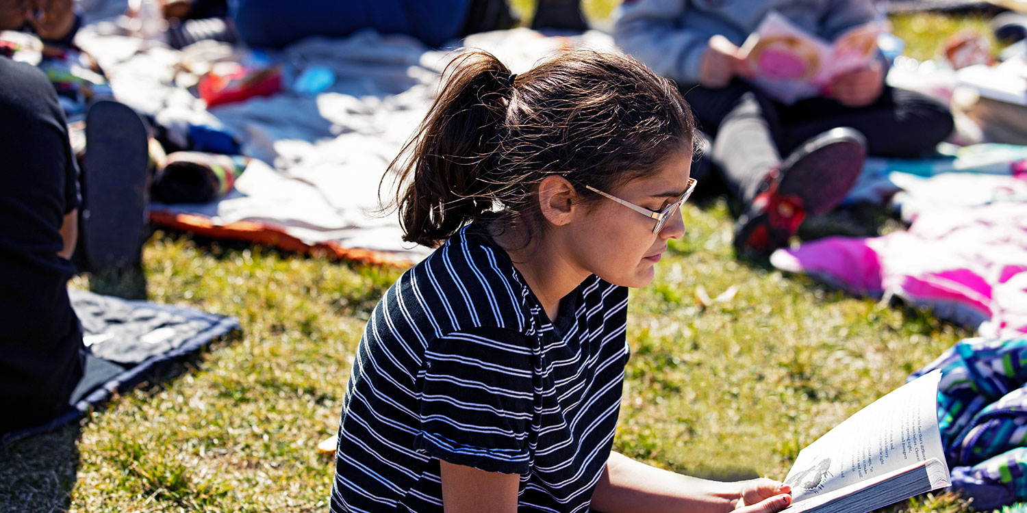 Students reading a books outside school on the lawn.